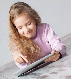 Child with tablet lying on floor