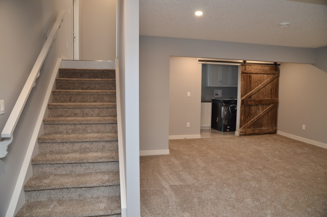 Bedrock Construction - Basement stairs with barn door into laundry room